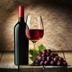 Rotweinglas mit Flasche und Rebe