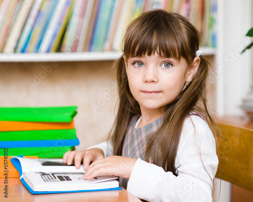 Young schoolgirl reading a book. looking at camera