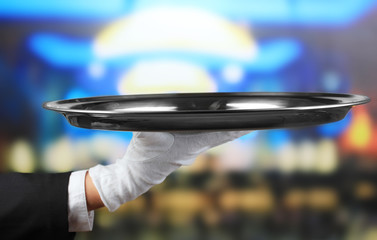 Empty tray in hand waiter on restaurant background
