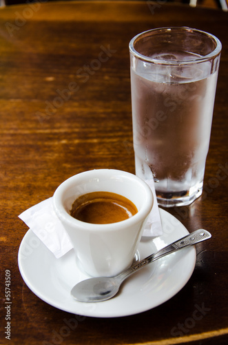 White espresso cup with glass of cold water on the wooden table