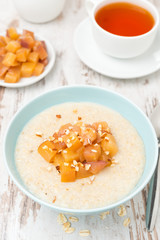 oatmeal with caramelized peaches and tea for breakfast, top view
