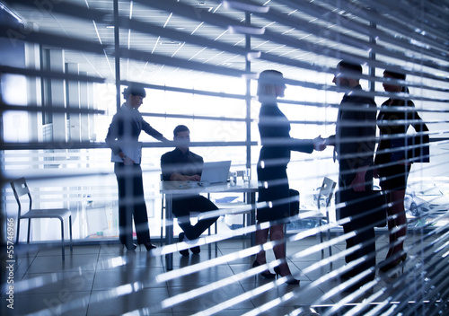 silhouettes of business people through the blinds
