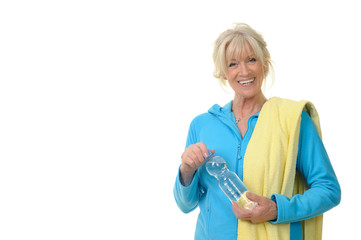Sportliche Seniorin erfrischt sich mit Getränk