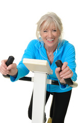 Sportliche Seniorin auf dem Hometrainer hört Musik