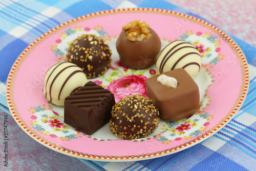 Selection of chocolates on pink porcelain plate, close up
