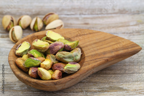 Pistachio nuts in miniature wooden bowl, close up