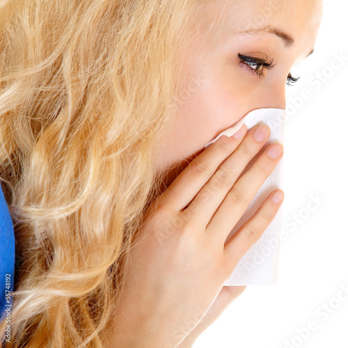 Young woman with cold sneezing into tissue over white