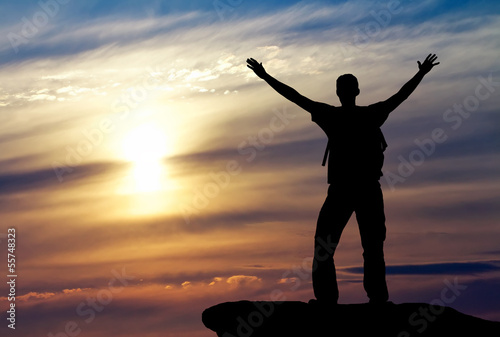 Silhouette of a man on a mountain top on sunset background