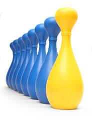 Yellow  bowling pin among common blue pins. Leadership metaphor.