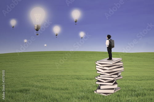 Business kid stand on books looking at lightbulbs outdoor