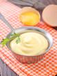 mayonnaise in metal spoon on wooden board
