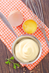 mayonnaise in metal spoon on wooden board