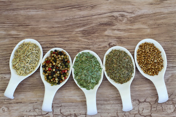 Selection of herbs and spices on spoons with copy space