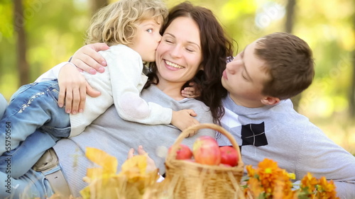 Happy family playing outdoors in autumn park. Dolly shot