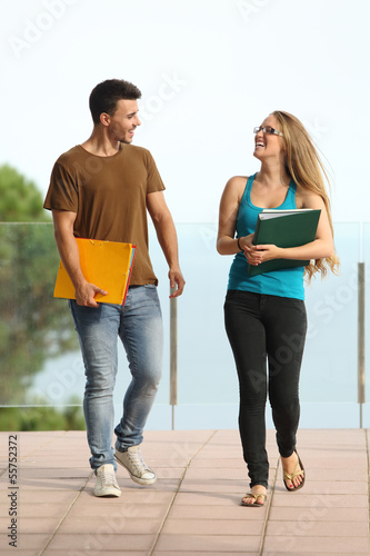 Teenager students boy and girl walking towards camera