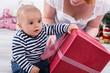 Erstes Weihnachtsfest mit Kind - Baby mit Geschenk