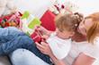 Familie; Mutter und Kind packen ein Weihnachtsgeschenk aus