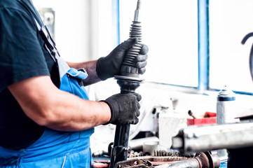 Auto car mechanic working on car shock absorber in car service