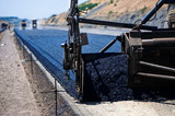 industrial pavement truck laying fresh asphalt