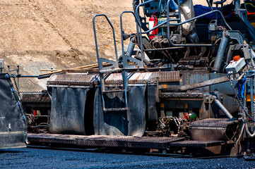 Qualified engineer operating asphalt paver machinery