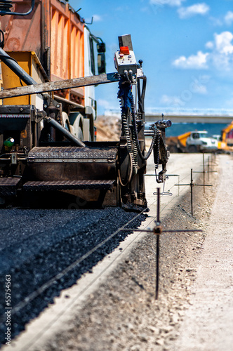 Industrial pavement truck or machine laying fresh bitumen