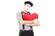 Sad mime artist holding a red heart