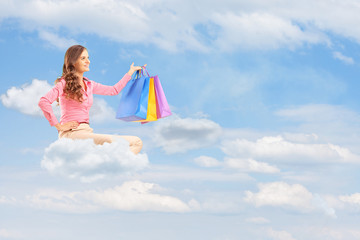 Young female flying on cloud and holding bags against cloudy sky