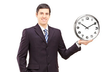 Young man in a suit holding a clock