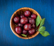 Ripe plums in a wooden bowl on a blue wooden background