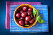 Plums in a wooden bowl on a vintage wooden background