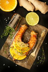 Grilled salmon, lime, orange and ginger on a  slate chalkboard