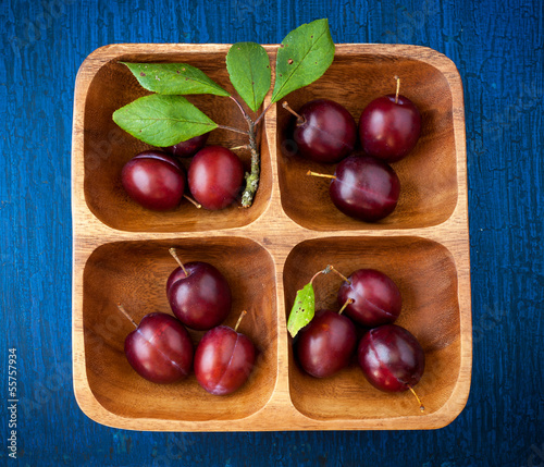 Plums in a wooden bowl on a blue wooden background