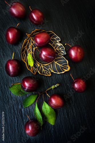 Ripe plums on a black slate chalkboard