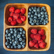 Raspberries and blueberries in a wooden bowl