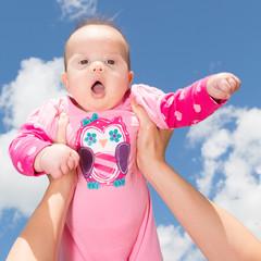 Little Baby Girl Against Cloudy Sky