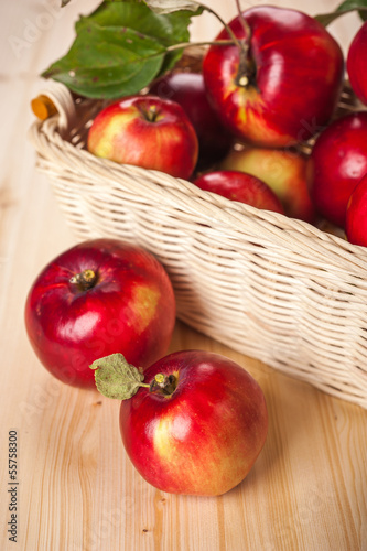 Ripe red apples in a basket on the table