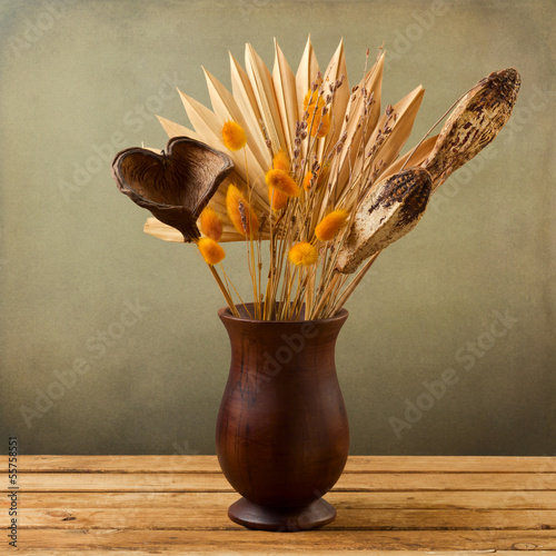 Tropical dried flowers in wooden vase over grunge background