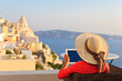 woman with touch pad in Santorini, travel concept