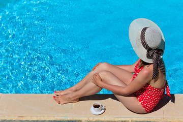 woman relaxed by the pool with cup of coffee