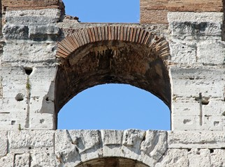ancient Arch of the Colosseum and the blue sky of Rome in Italy