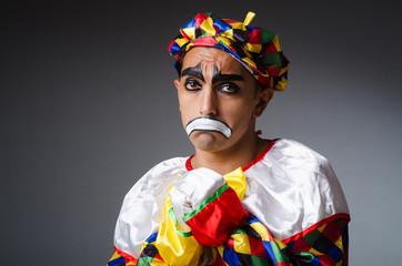 Sad clown against dark background