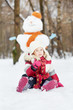 Little girl sits on snow in front of big snowman in winter park,