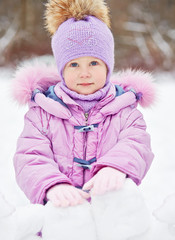 Portrait of little girl who stands behind wall made from snow