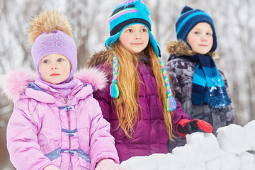 girl and two older children stand behind wall of snow blocks