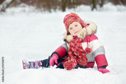 Little girl sits on snow in winter park
