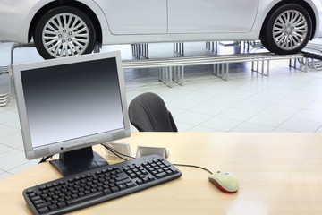 Computer stands on wooden desk and new car stands in office