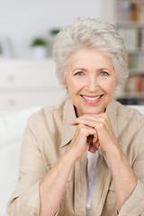 lächelnde seniorin stützt kinn auf