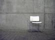 weißer stuhl vor betonwand