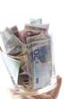 Hand hält Glas mit Euro-Banknoten