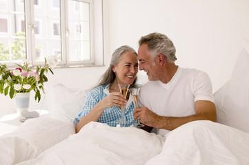 Älteres Paar auf dem Bett mit Champagner, lächelnd